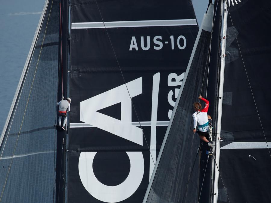 I concorrenti si arrampicano sugli alberi mentre le barche a vela competono durante la regata Barcolana di fronte al porto di Trieste. (REUTERS/Alessandro Garofalo)