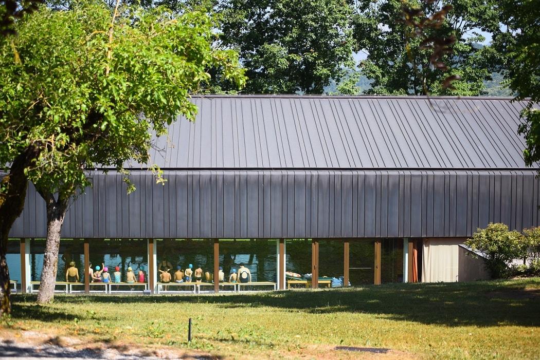 Anche la piscina è immersa nel verde su cui le enormi vetrate a tutta parete si affacciano