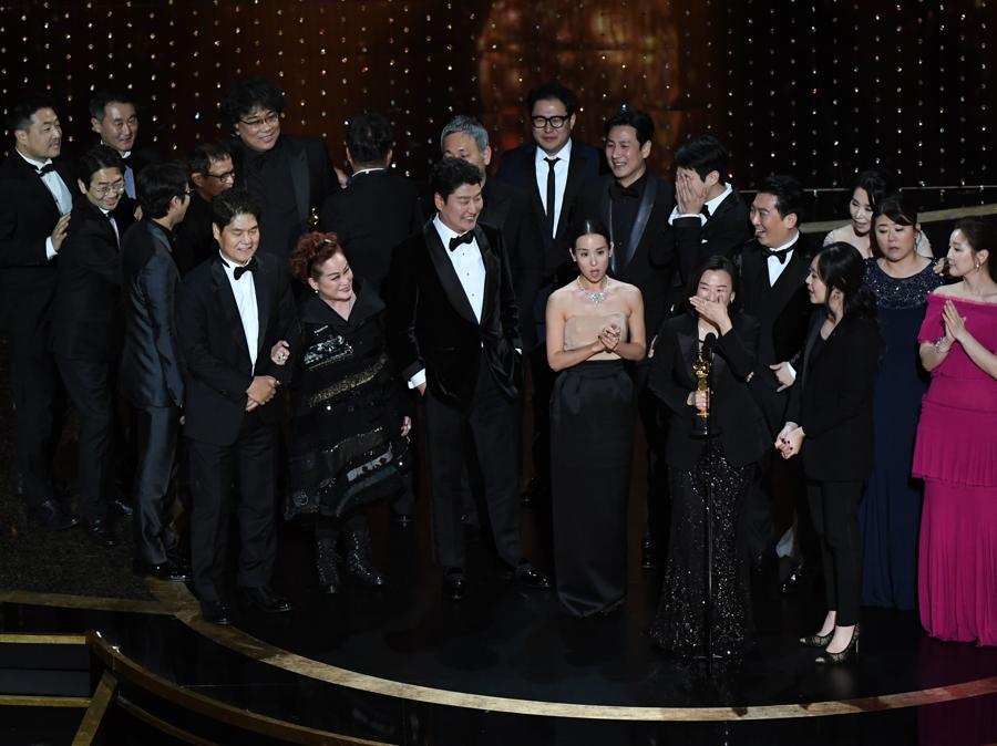"""Il cast e la troupe di """"Parasite"""" ricevono il premio per il miglior film. (Photo by Mark RALSTON / AFP)"""