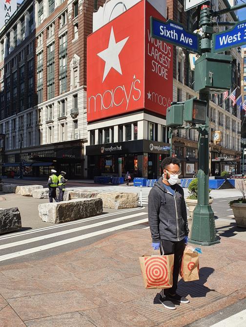 Un ragazzo con le buste della spesa e la mascherina davanti ai magazzini Macy's.