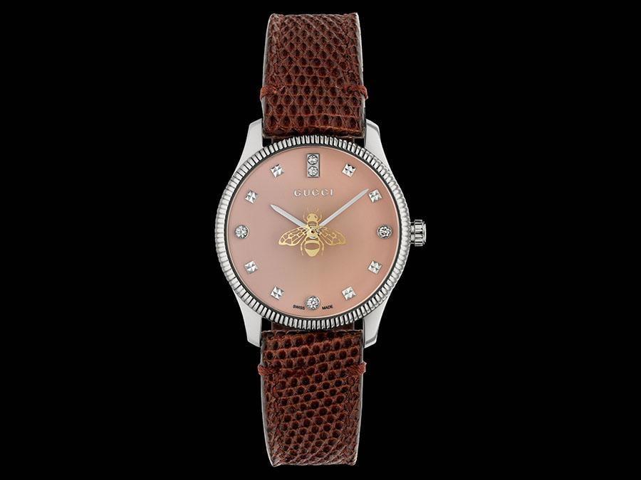 Gucci Timepieces. Al centro del quadrante laccato rosa di questa nuova variante di G-Timeless Slim non si trova la lancetta dei secondi ma l'ape di Gucci che, girando, ne ricopre il ruolo. Cassa in acciaio, diamanti sul quadrante e cinturino in pelle.
