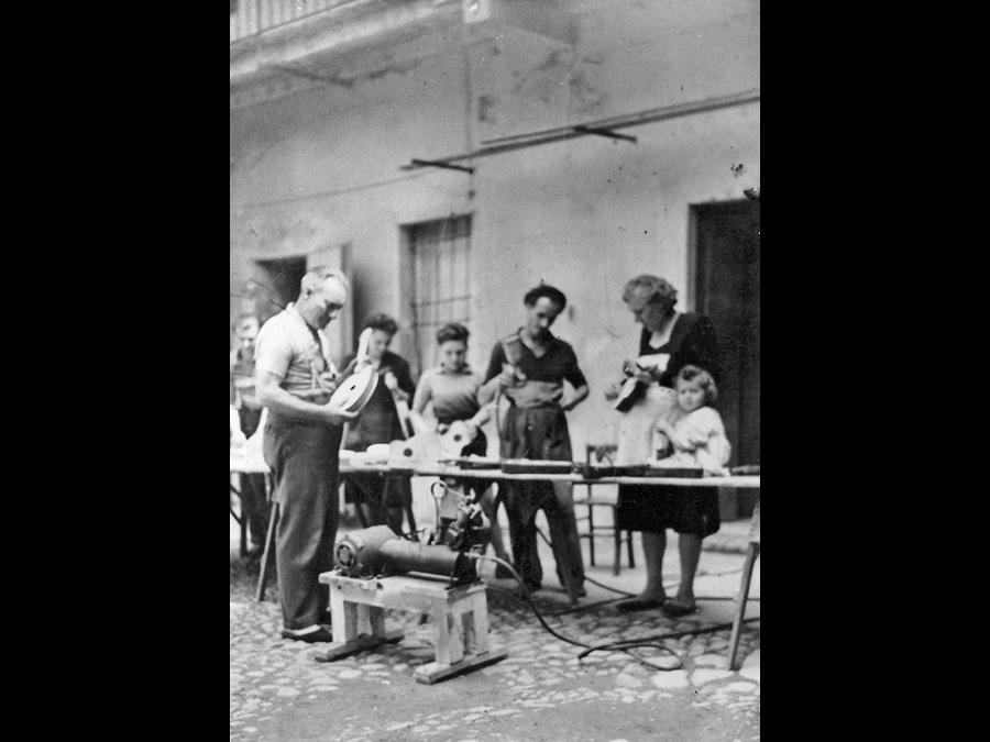 El Bûtunin. Inizio anni 50: sotto la ringhiera della curt del Sachèt dove si apriva il retro del negozio del Bûtunin tutta la famiglia è impegnata a fabbricare giocattoli in legno