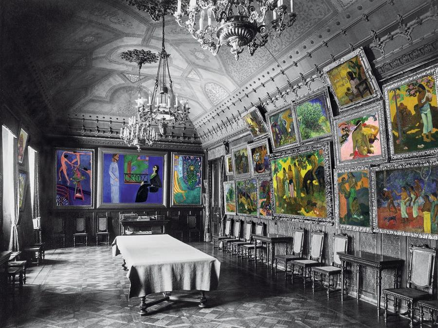 """La sala da pranzo ospitava in gran numero le opere di Paul Gauguin, le quali formavano una vera e propria """"iconostasi"""". Accanto a quest'ultime, in maniera inedita, comparivano anche dei Van Gogh. La parete di fondo invece era dedicata a Henri Matisse, con un trittico composto da Les Capucines à La Danse, La Conversation e Coin d'Atelier. (Colorizzazione delle foto degli archivi di famiglia: © Christine Delocque-Fourcaud)"""