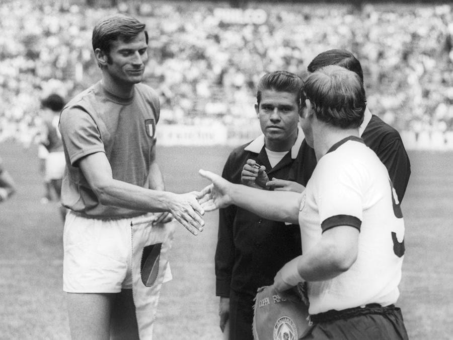 I capitani di Italia e Germania, Giacinto Facchetti  e Uwe Seeler, si stringono la mano prima del calcio d'inizio (Afp)
