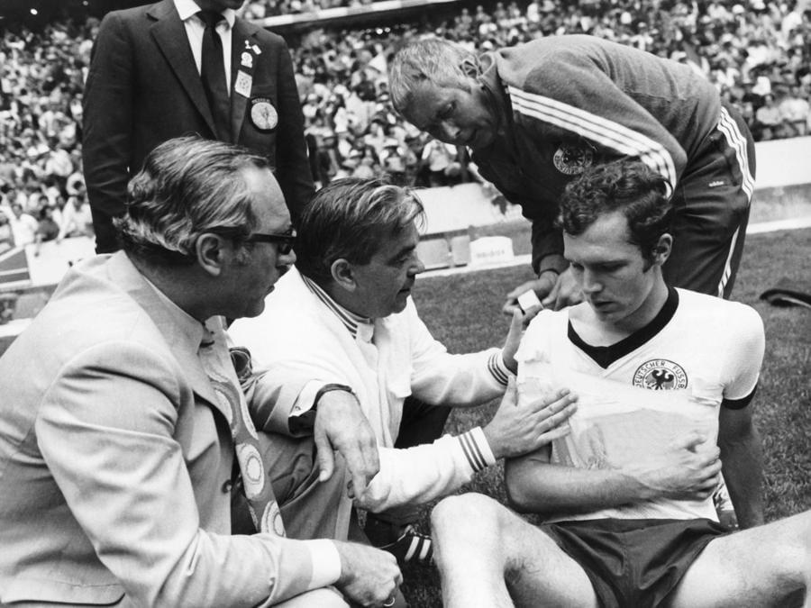 Franz Beckenbauer viene curato alla spalla dopo uno scontro in campo (Photo by DB/picture alliance via Getty Images)