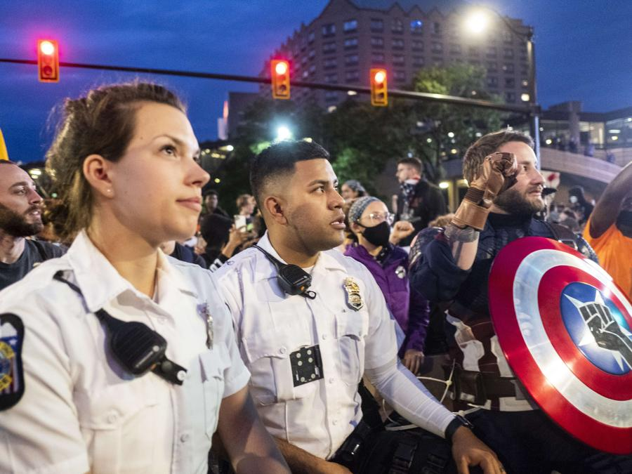 Ufficiale di Columbus Police Department in ginocchio per 'The Lord's Prayer'  in Columbus, Ohio. (Matthew Hatcher/Getty Images/AFP)