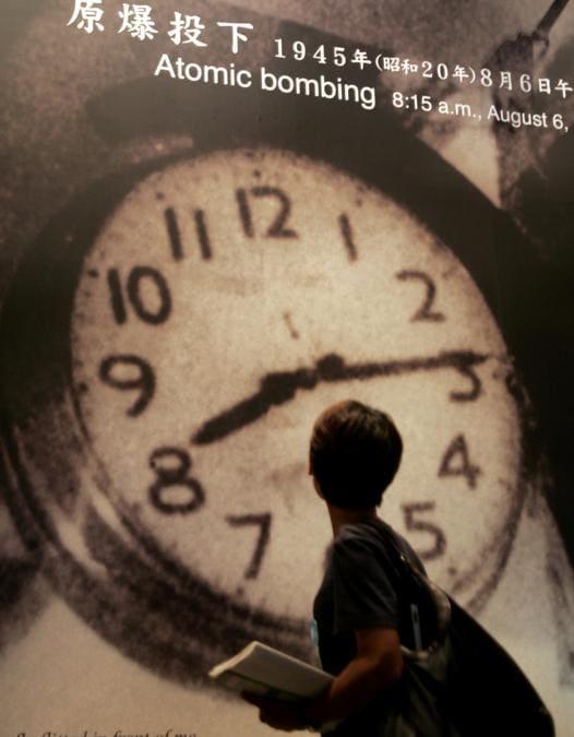 Un visitatore del Museo della Pace di Hiroshima, guarda un grande cartello che mostra l'ora esatta in cui la bomba atomica ha colpito la città giapponese: alle 8 e15 (REUTERS/Yuriko Nakao)