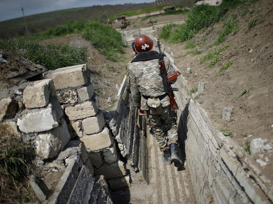 I soldati di etnia armena camminano in una trincea nella loro posizione vicino al confine del Nagorno-Karabakh. (REUTERS)
