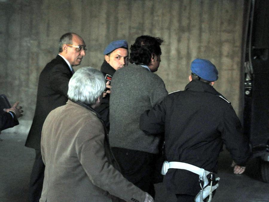 Il comandante della Costa Concordia Francesco Schettino (al centro tra due agenti di polizia penitenziaria) al termine dell'interrogatorio a Palazzo di Giustizia di Grosseto, 17 gennaio 2012, si dirige verso il cellulare della polizia per tornate in carcere dove attendera' la decisione del Gip. ANSA/ENZO RUSSO