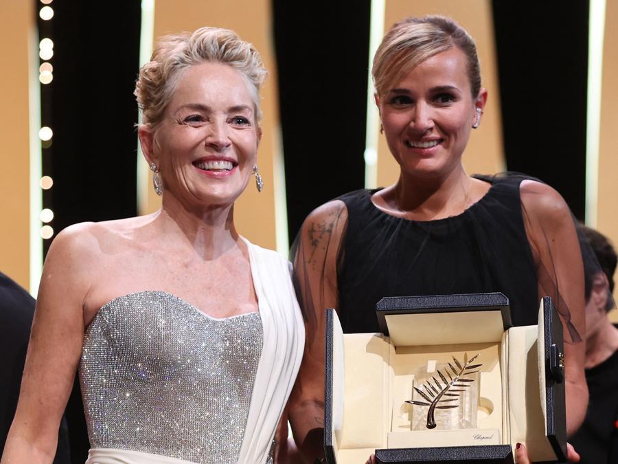 """La regista francese Julia Ducournau (a destra) posa sul palco con l'attrice statunitense Sharon Stone dopo aver vinto la Palma d'oro per il suo film """"Titane"""" durante la cerimonia di chiusura della 74a edizione del Festival di Cannes . (Photo by Valery HACHE / AFP)"""