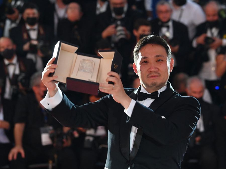 """Il regista giapponese Ryusuke Hamaguchi posa dopo aver vinto il premio per la migliore sceneggiatura per il film """"Drive My Car"""", durante la cerimonia di chiusura della 74a edizione del Festival di Cannes. (Photo by CHRISTOPHE SIMON / AFP)"""