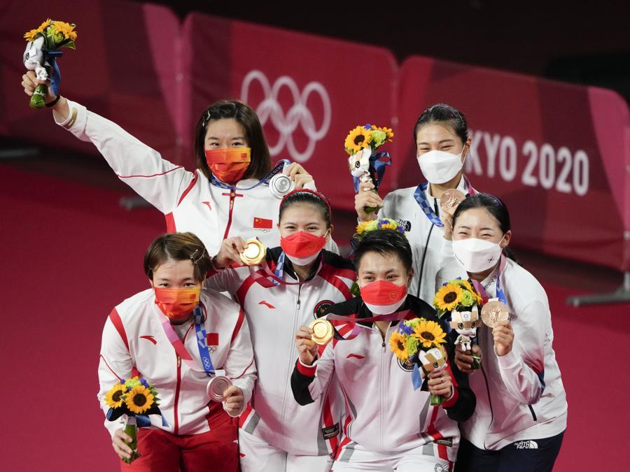 Da sinistra: medaglia d'argento le cinesi, medaglia d'oro le indonesiane e medaglia di bronzo le sud coreane festeggiano sul podio del doppio femminile di  badminton  (AP Photo/Markus Schreiber)