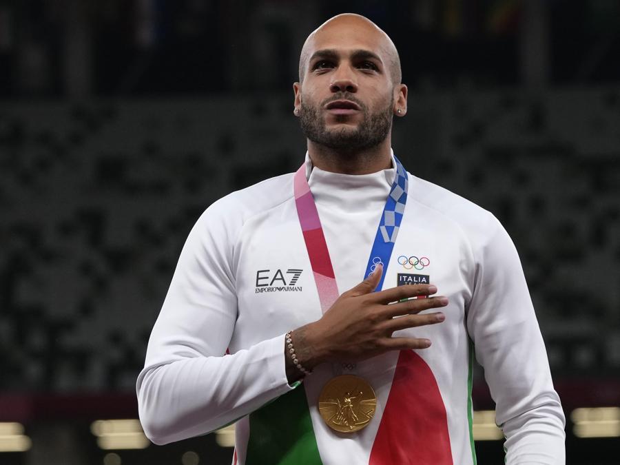 L'italiano Lamont Jacobs, sul podio con la medaglia d'oro vinta nella finale dei  100m piani (AP Photo/Francisco Seco)