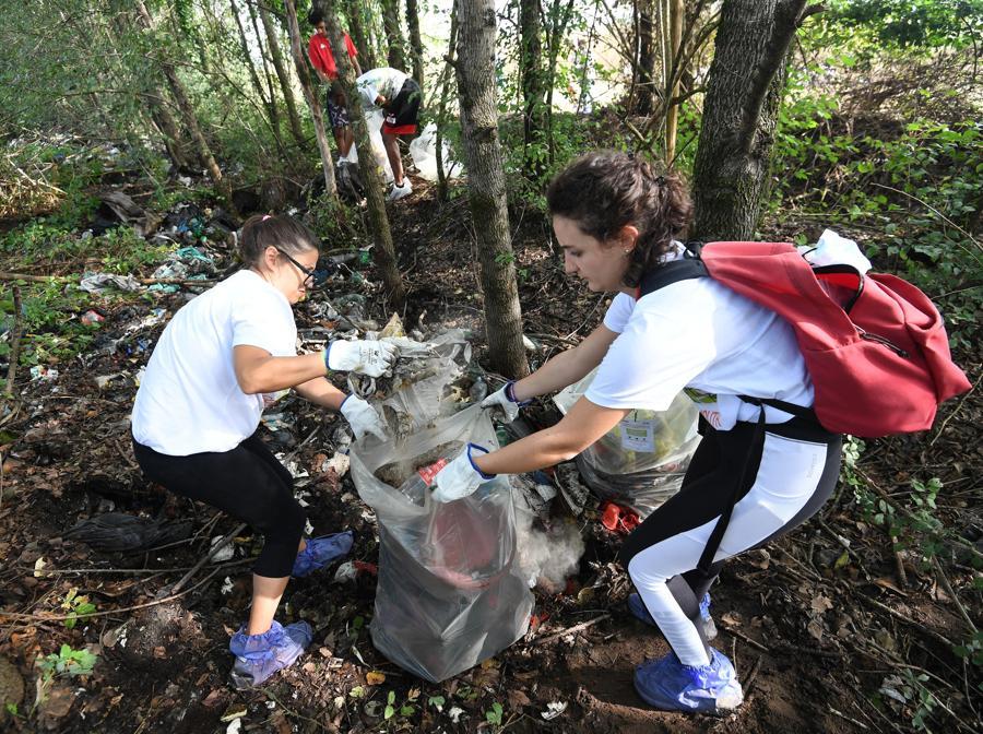 """Giovani raccolgono i rifiuti abbandonati nell'area della Casa Chiaravalle nel giorno di apertura di """"Youth4ClimateCoop Youth Experience. (ANSA/DANIEL DAL ZENNARO)"""