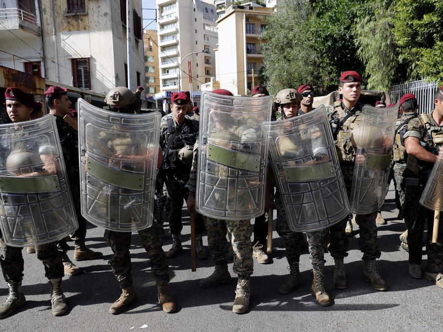 L'esercito libanese fa la guardia vicino al Palazzo di Giustizia mentre i sostenitori dei gruppi sciiti Hezbollah e Amal protestano contro il giudice Tarek Bitar che sta indagando sull'esplosione mortale del porto marittimo dello scorso anno, a Beirut, in Libano (AP Photo/Hussein Malla)
