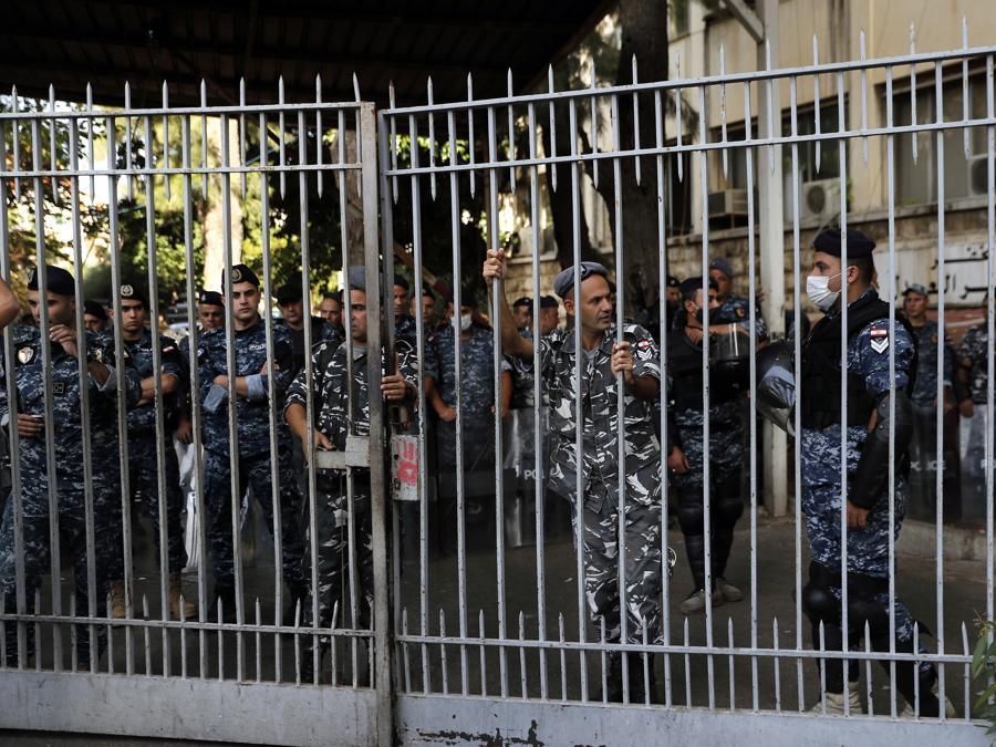 I poliziotti fanno la guardia all'interno del Palazzo di Giustizia mentre i sostenitori dei gruppi sciiti Hezbollah e Amal protestano contro il giudice Tarek Bitar che sta indagando sull'esplosione mortale del porto marittimo dello scorso anno, a Beirut, in Libano (AP Photo/Hussein Malla)
