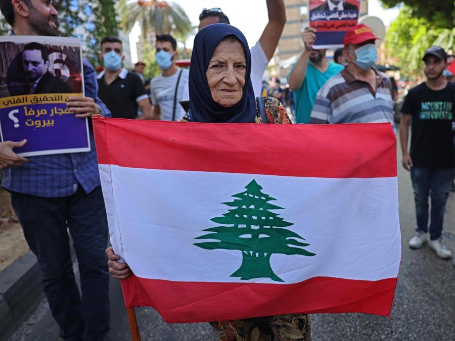 Una sostenitrice di Hezbollah e del movimento Amal sventola la bandiera nazionale vicino al Palazzo di Giustizia nella capitale Beirut il 14 ottobre 2021, durante una riunione per chiedere il licenziamento dell'investigatore capo dell'esplosione di Beirut. (Photo by JOSEPH EID / AFP)