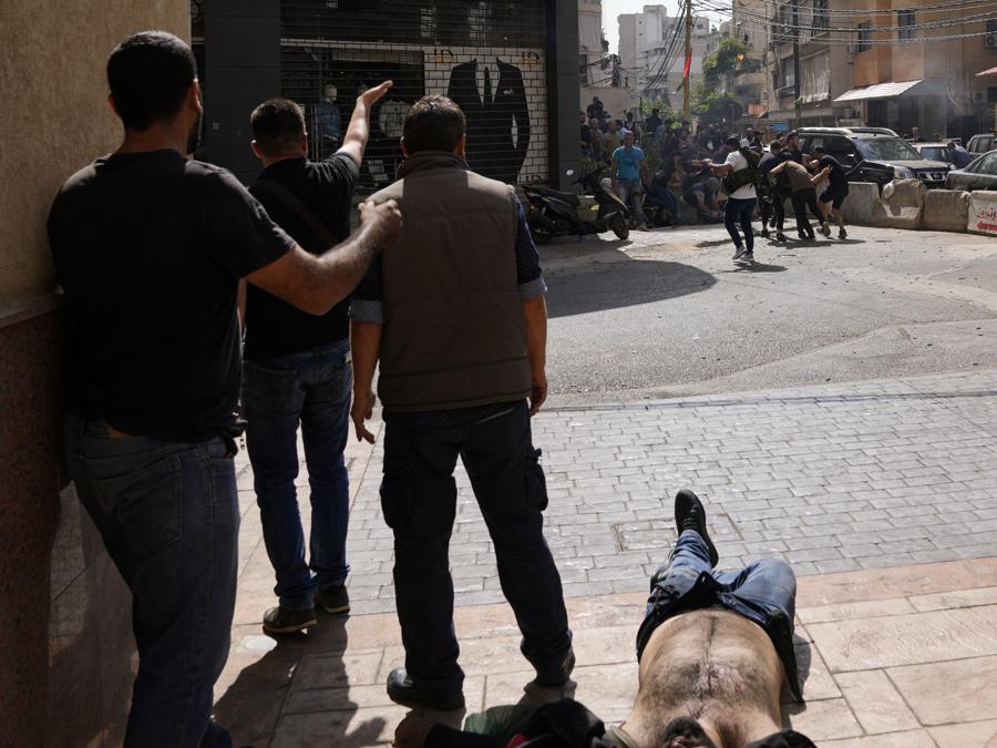 sostenitori di un gruppo sciita alleato di Hezbollah chiedono aiuto per un compagno ferito durante gli scontri armati scoppiati durante una protesta nel sobborgo meridionale di Beirut di Dahiyeh, in Libano, giovedì 14 ottobre 2021. Non è stato immediatamente chiaro cosa abbia innescato la sparatoria , ma le tensioni erano alte lungo un'ex prima linea di guerra civile tra aree musulmane sciite e cristiane. (AP Photo/Hassan Ammar)