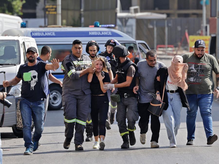Medici libanesi aiutano a evacuare i civili durante gli scontri nella zona di Tayouneh, nel sobborgo meridionale della capitale Beirut, il 14 ottobre 2021, a seguito di una manifestazione dei sostenitori di Hezbollah e del movimento Amal. - Gli spari hanno ucciso almeno tre persone e ne hanno ferite 20 durante una manifestazione a Beirut organizzata dai movimenti sciiti Hezbollah e Amal per chiedere il licenziamento dell'investigatore capo dell'esplosione di Beirut. (Photo by JOSEPH EID / AFP)