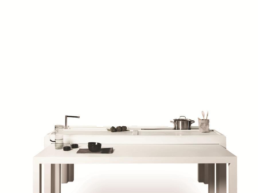 TM Italia, Off Kitchen, design Daniele Bedini. Cucina utilizzabile sia indoor che outdoor. Il piano di lavoro con un semplice gesto diventa tavolo da pranzo per poi trasformarsi in cucina completa di piano cottura e lavello. Il tavolo centrale è dotato di un piano estraibile che ne raddoppia la superficie. All'interno del piano sono contenuti un lavello e un piano di cottura a induzione, cui si accede attraverso pratiche ante a ribalta. Il tavolo è interamente realizzato in Corian.