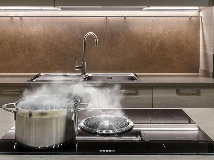 Frigo2000, piano di cottura a induzione Bora con Biu, aspiratore filtrante centrale, di grande efficacia e potenza per chi cucina sovente impegnando gran parte delle zone di cottura; l'aspiratore ha due filtri al carbone, un filtro per i grassi a 8 strati, lo ionizzatore e la spia per i necessari interventi.