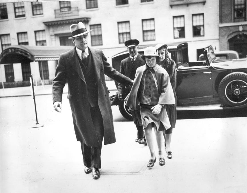 In questa foto del 22 aprile 1935, accompagnata da una guardia del corpo, un'infermiera e un'autista, Gloria Vanderbilt entra nella casa di sua madre, Gloria Morgan Vanderbilt, nel centro di Manhattan, New York (AP Photo)