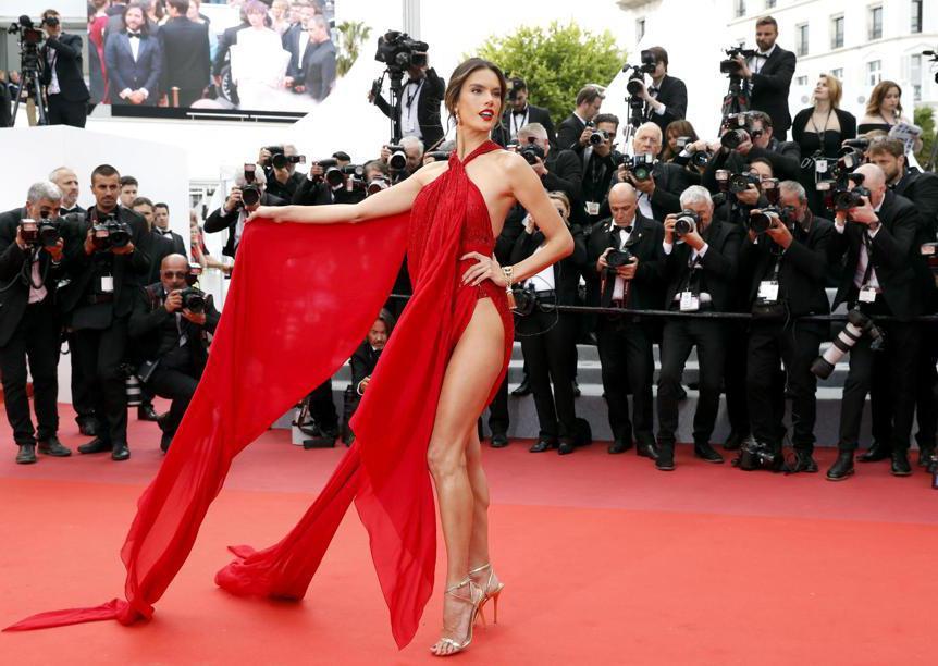 """La seconda serata del festival del cinema di Cannes ha visto passare sul red carpet una serie di abiti """"svolazzanti"""" e piuttosto scenografici, come quello di Alessandra Ambrosio, in rosso Julien MacDonald"""