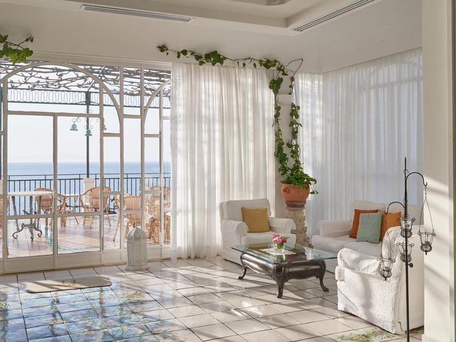 Il salotto con ampie vetrate, e maioliche dipinte a mano. Ha anche un angolo con il camino. Un dettaglio che fa molto piacere nelle serate più fresche di primavera e autunno.
