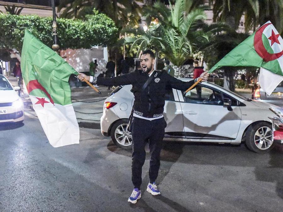 Un algerino mostra le bandiere nazionali per le strade di Algeri (Afp/Ryad Kramdi)