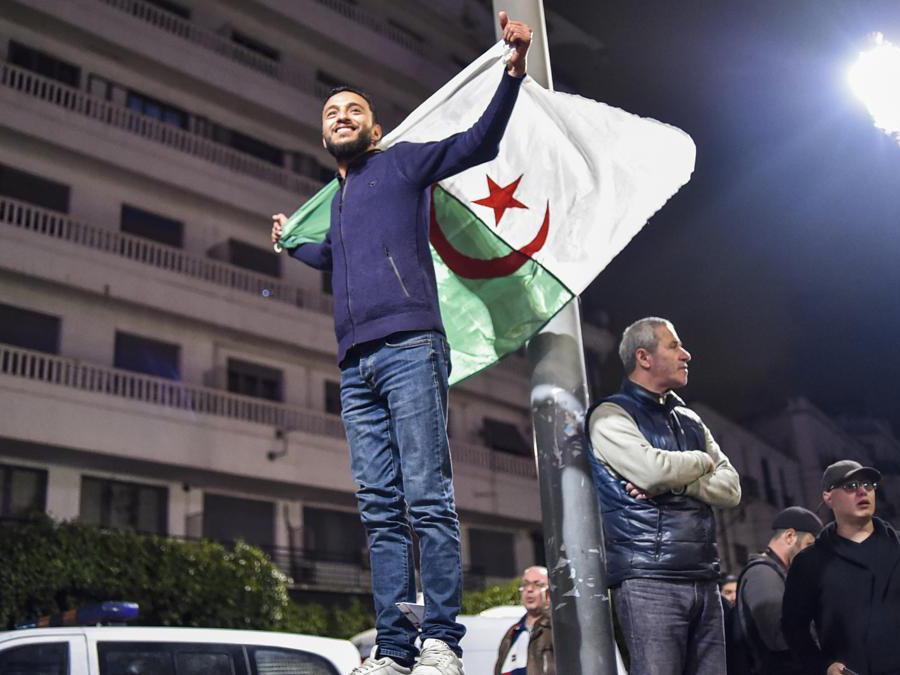 Un algerino mostra la bandiera nazionale per le strade di Algeri (Afp/Ryad Kramdi)