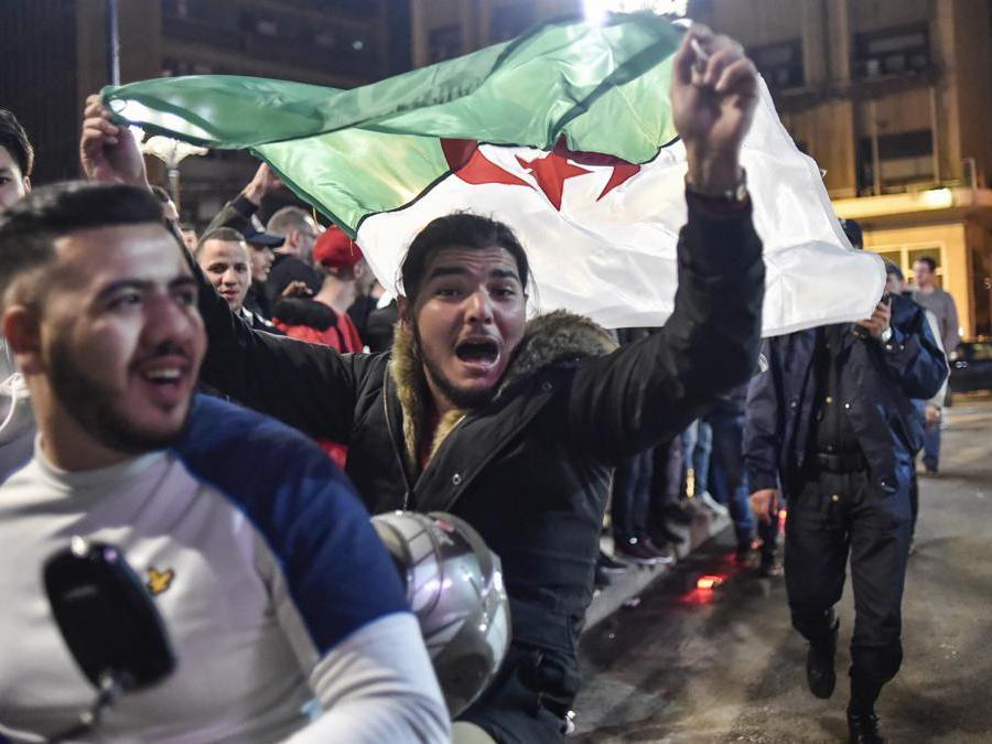 Due algerini su di un scooter per le strade di Algeri mostrano la bandiera nazionale (Afp/Ryad Kramdi)