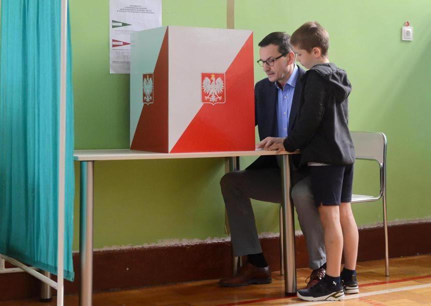 Il primo ministro polacco Mateusz Morawiecki  con il figlio (Jakub Kaminski/Epa)