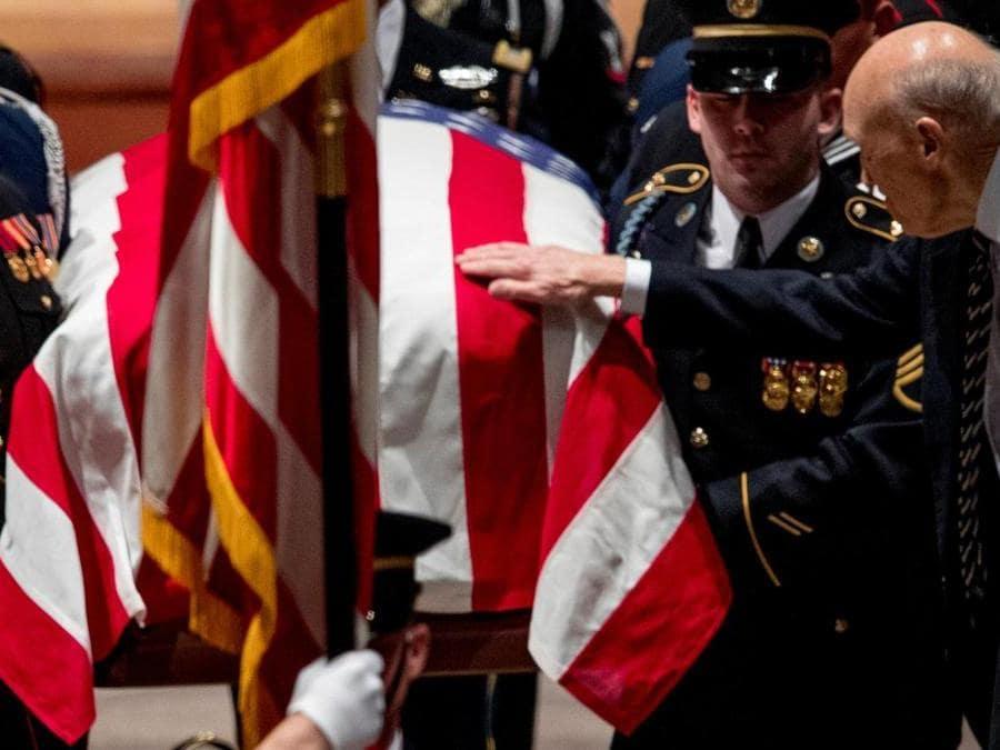 Il senatore . Alan Simpson (R-WY)tocca la bandiera che avvolge la bara del Presidente  George H.W. Bush  Andrew Harnik/Pool via REUTERS
