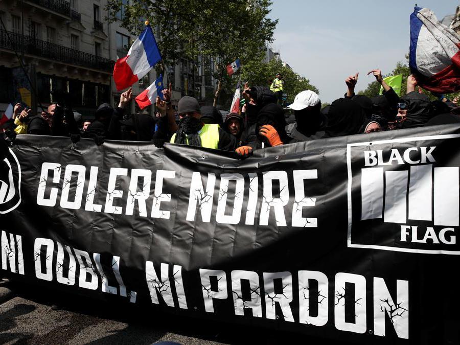 manifestanti mascherati assistono a una dimostrazione durante la tradizionale giornata dei lavoratori del primo maggio a Parigi, Francia.  REUTERS/Benoit Tessier