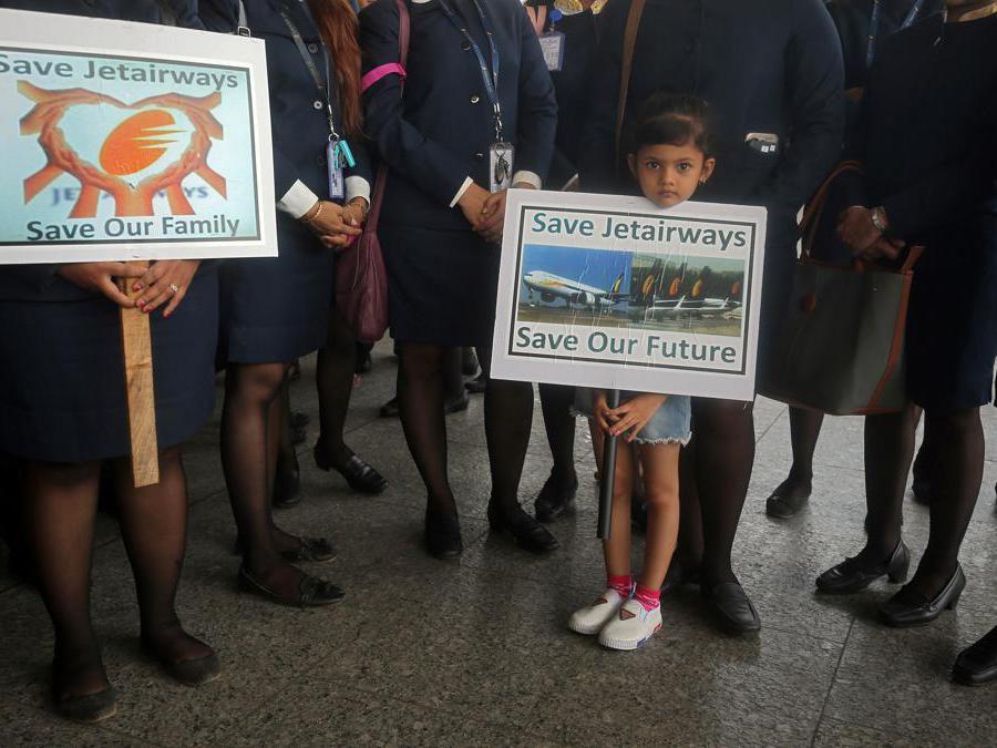 """Keren Rodriguez, 6 anni, figlia di un dipendente della Jet Airways, tiene un cartello mentre partecipa a una protesta dei dipendenti della Jet Airways che chiedono di """"salvare Jet Airways"""" in occasione del Primo Maggio all'Aeroporto Internazionale Chhatrapati Shivaji Maharaj a Mumbai, in India. REUTERS/Francis Mascarenhas"""