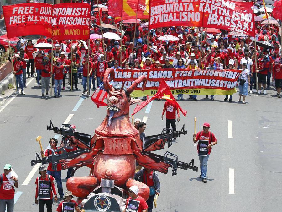 Migliaia di lavoratori marciano con un'effigie del Presidente Rodrigo Duterte verso il Palazzo Presidenziale a Manila, nelle Filippine, per rendere omaggio ai lavoratori in celebrazione della Giornata Internazionale del Lavoro. (AP Photo/Bullit Marquez)