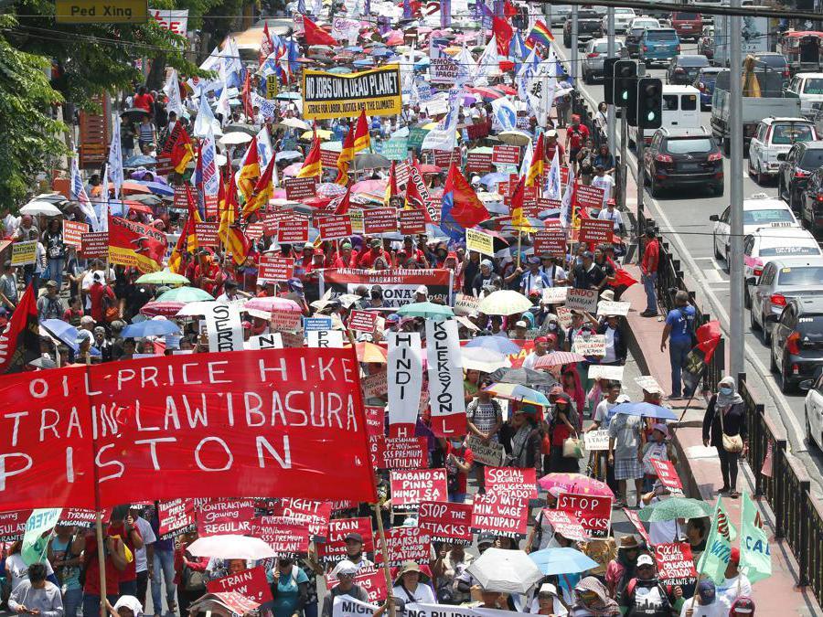 Migliaia di lavoratori manifestano il loro messaggio mentre marciano verso il palazzo presidenziale a Manila, nelle Filippine, per rendere omaggio ai lavoratori in occasione della Giornata internazionale del lavoro. (AP Photo/Bullit Marquez)