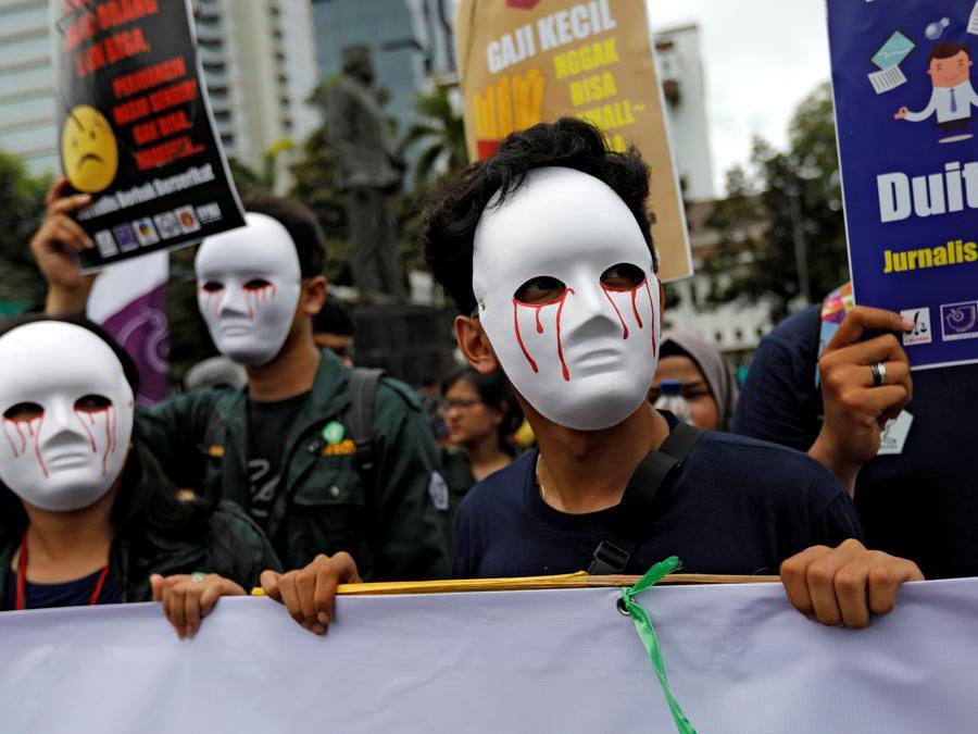 Giornalisti indonesiani indossano maschere mentre protestano durante un raduno del Primo Maggio vicino al Monumento Nazionale (Monas) a Giacarta, Indonesia. REUTERS/Willy Kurniawan