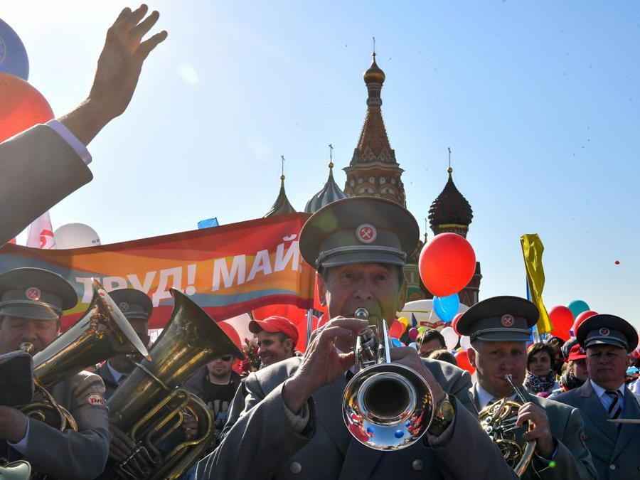 I membri dei sindacati russi che tengono palloncini, bandiere e fiori artificiali sfilano sulla Piazza Rossa durante la loro manifestazione del Primo Maggio a Mosca . (Photo by Yuri KADOBNOV / AFP)