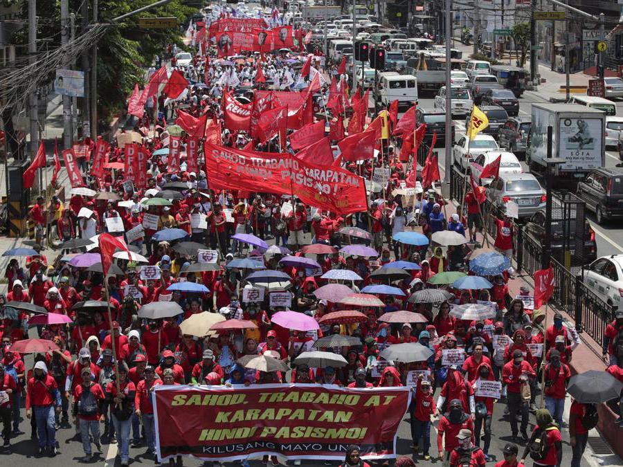 I manifestanti marciano su una strada in occasione della festa del lavoro a Manila, Filippine. EPA/FRANCIS R. MALASIG