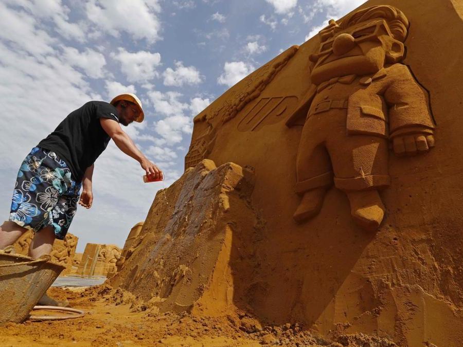 """Teimur Abdul Ganiev dalla Russia lavora su una scultura  durante il Festival della scultura di sabbia """"Disney Sand Magic"""" a Ostenda. (Reuters)"""