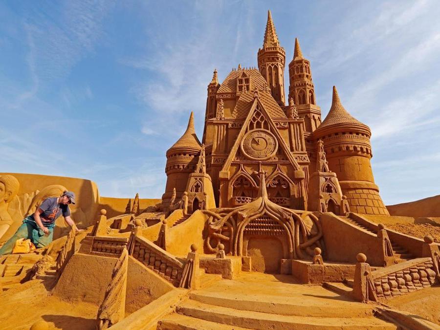 """Susanne Paucker dalla Germania lavora su una scultura  durante il Festival della scultura di sabbia """"Disney Sand Magic"""" a Ostenda. (Reuters)"""