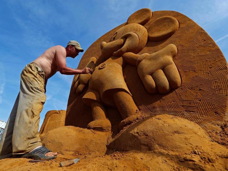 """Konstantin Kuzyarin dalla Russia lavora su una scultura  durante il Festival della scultura di sabbia """"Disney Sand Magic"""" a Ostenda. (Reuters)"""