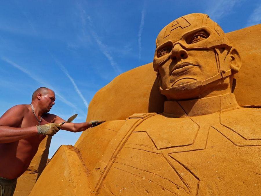 """Sergey Zaplatin dalla Russia lavora su una scultura  durante il Festival della scultura di sabbia """"Disney Sand Magic"""" a Ostenda. (Reuters)"""