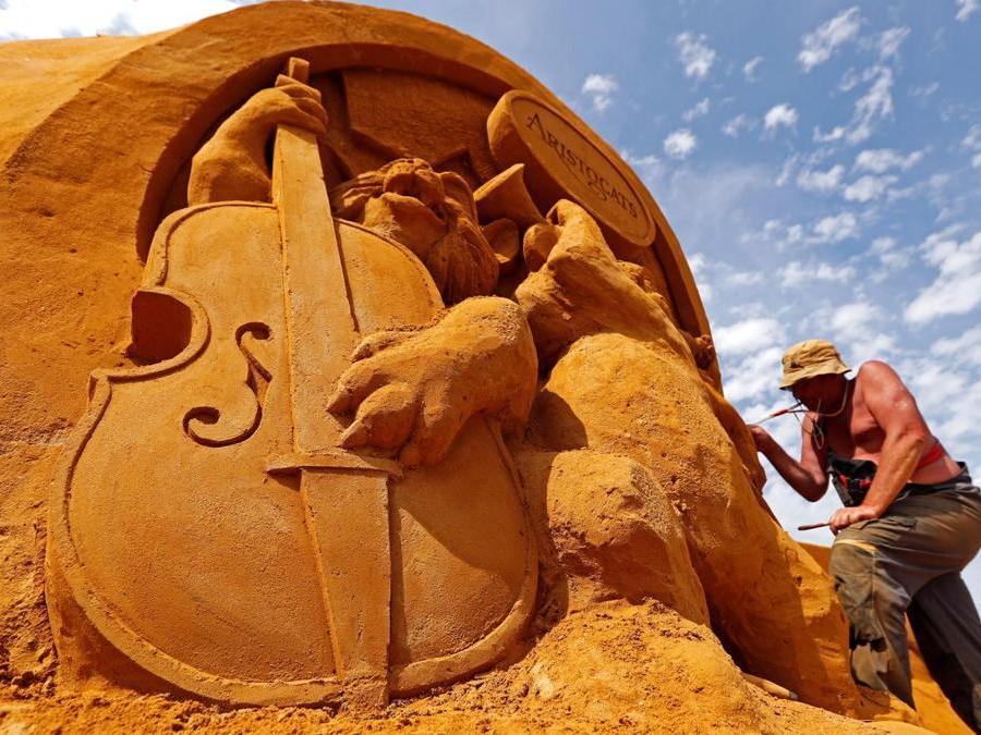 """Sergey Aseer dalla Russia lavora su una scultura  durante il Festival della scultura di sabbia """"Disney Sand Magic"""" a Ostenda. (Reuters)"""
