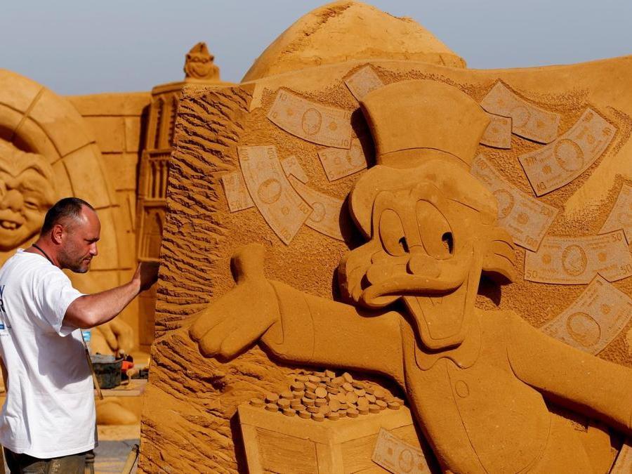 """Teimur Ilya Shanin dalla Russia lavora su una scultura  che raffigura Zio PAperone durante il Festival della scultura di sabbia """"Disney Sand Magic"""" a Ostenda. (Reuters)"""