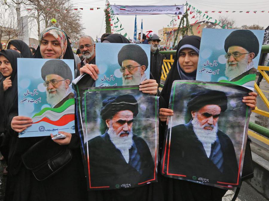 Le donne iraniane posano con i ritratti del leader supremo del paese Ali Khamenei e il suo predecessore (Afp)