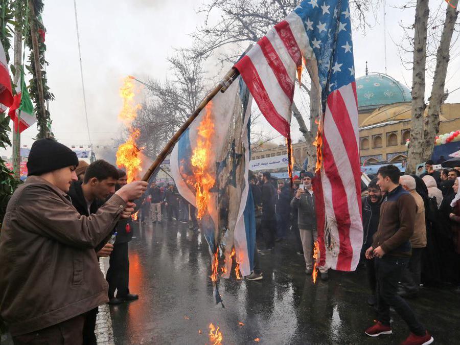 Gli iraniani bruciano le bandiere di Israele e degli Stati Uniti durante le commemorazioni del 40 ° anniversario della rivoluzione islamica nella capitale Teheran (Afp)