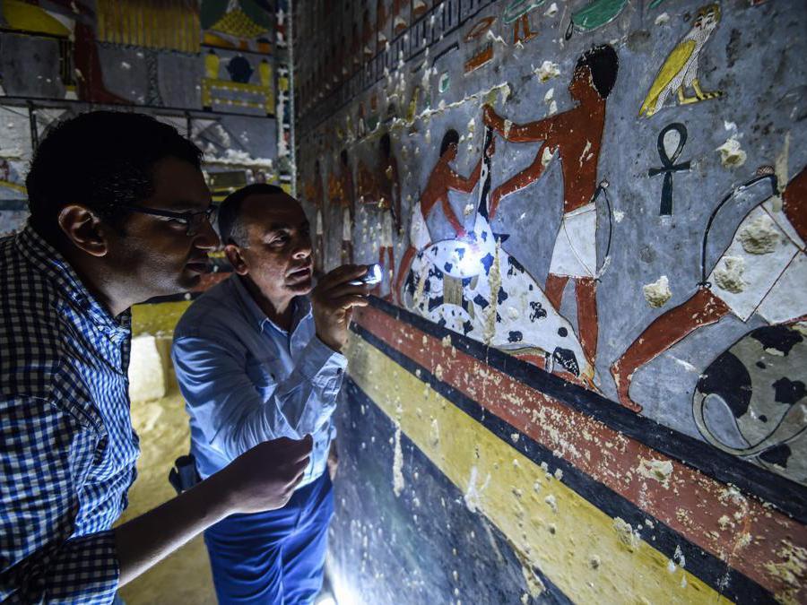 """Mohamed Mujahid (sinistra), capo della missione egiziana che ha scoperto la tomba dell'antico nobile egiziano """"Khewi"""" risalente alla V dinastia (2494-2345 aC), ispeziona le mura della tomba all'interno della necropoli di Saqqara. (Photo by Mohamed el-Shahed / AFP)"""