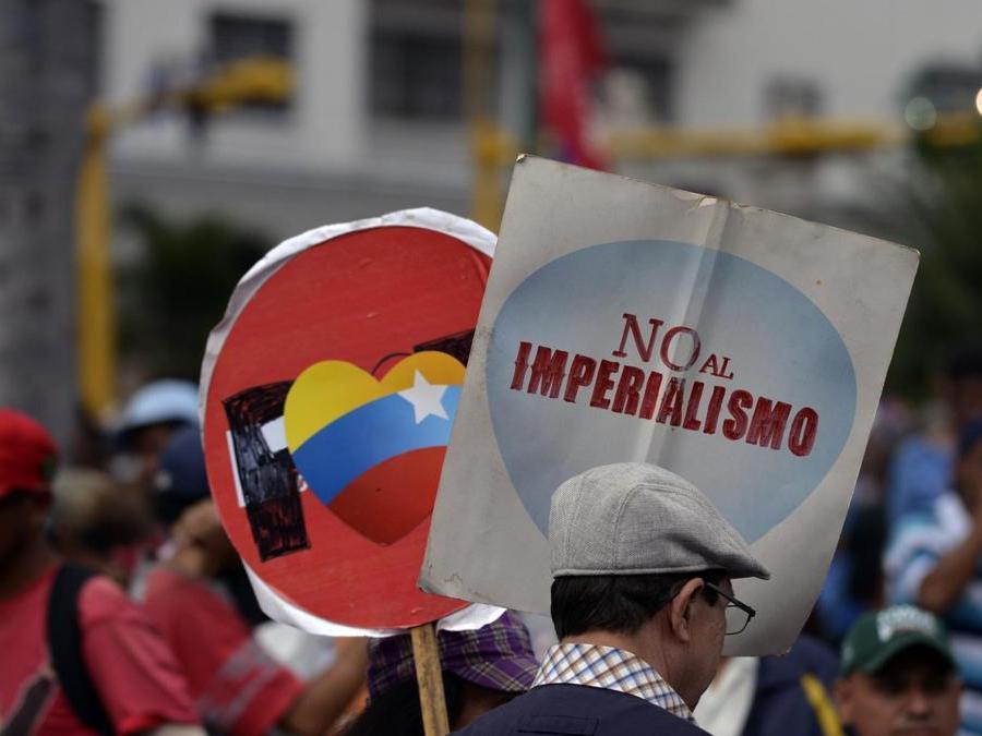 "Un supporter  di Maduro con in mano un cartello con la scritta ""No all'Imperialismo"" (Photo by Luis ROBAYO / AFP)"